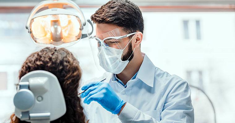 Dental team member working on patient wearing PPE during coronavirus.